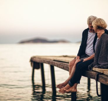 Loving senior couple enjoying the life and eachother, sitting on the dock by the seaside